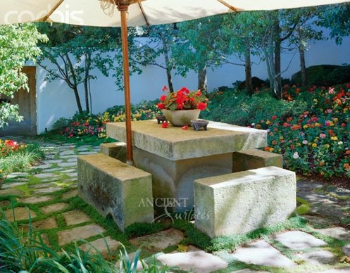 Concrete slab patio table and benches on moss and stone covered patio walkway