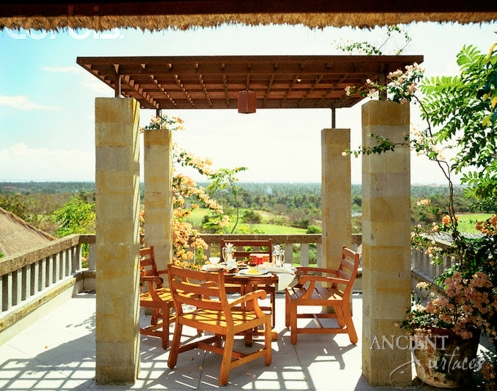 Alfresco dining under a portico supported by stone pillars, on a resort in Bali